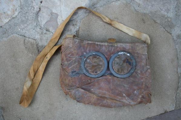 Don de Mr Pierre et la famille DE VOLONTAT de Conilhac Corbières. Masque M2 deuxième modèle ( M2B ). A partir du 24 janvier 1916, la plaque de vision est modifiée en raison de sa fragilité et comporte désormais 2 oeillères saillantes munies chacune d'un viseur amovible fixé par une rondelle fixe-vitre en caoutchouc, du type utilisé pour les lunettes. On remarque cependant ici le cerclage métallique à compter du 21 juillet 1916. Sur cet cet exemplaire , on note également la sangle supplémentaire passant derrière la nuque, bien visible au milieu du masque ( photo intérieur ).