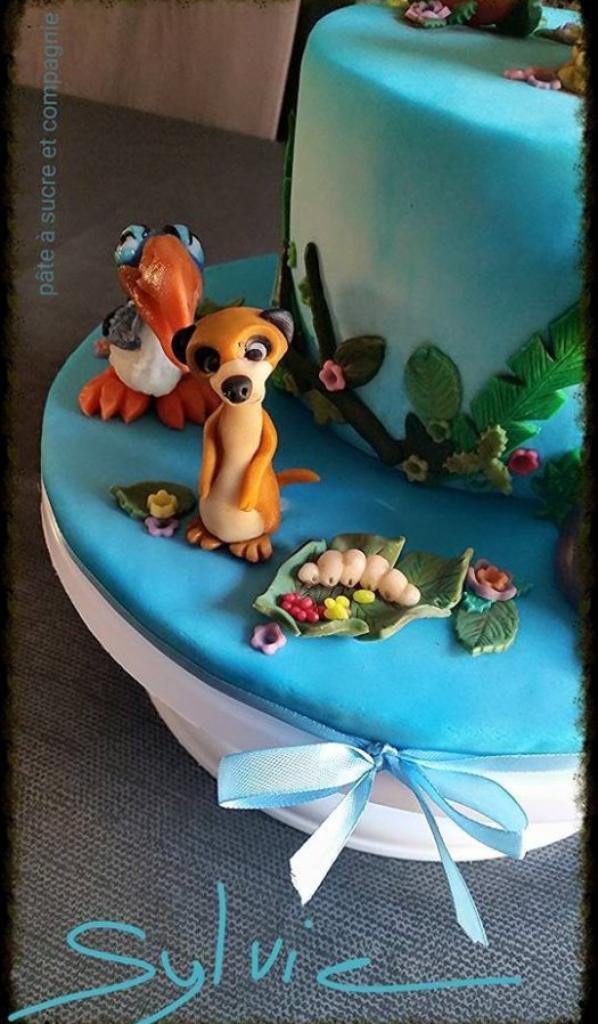 scene avec decor en pate a sucre representant le roi lion de disney a depose sur un gateau d anniversaire