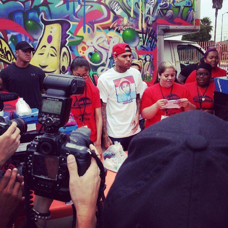 Distribution de chaussures à Campanella Park dans Compton et pose devant la nouvelle peinture de sa lamborghini.