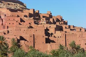 Situé sur les contreforts des pentes méridionales du Haut Atlas dans la province de Ouarzazate, le site d'Aït-Ben-Haddou est le plus célèbre des ksour de la vallée de l'Ounila. Le Ksar d'Aït-Ben-Haddou est un exemple frappant de l'architecture du sud marocain. Le Ksar est un groupement d'habitations essentiellement collectif. À l'intérieur de murailles défensives renforcées de tours d'angle et percées d'une porte en chicane, se pressent de nombreuses maisons d'habitation, les unes modestes, les autres faisant figure de petits châteaux urbains avec leurs hautes tours d'angle décorées à la partie supérieure de motifs décoratifs en brique crue, mais aussi des bâtiments et des espaces communautaires. C'est un extraordinaire ensemble de bâtiments offrant un panorama complet des techniques de construction en terre présahariennes. Il est difficile de préciser l'époque de la construction d'Aït Ben Haddou, mais l'occupation humaine de la région renvoie à la plus haute antiquité. Quant aux témoignages historiques, c'est à partir de l'époque almoravide, au cours des XIe et XIIe siècles, qu'ils prennent de l'épaisseur. On sait que dans cet « ighrem » cohabitait selon un système hiérarchique très élaboré une population amazighophone composée de Blancs et de Noirs, de Juifs et de Musulmans. L'ancien ksar, qui était encore occupé aux lendemains de l'indépendance du Maroc, en 1956, sera progressivement déserté par la population qui préférera construire un nouveau village sur la rive droite de l'Assif Marghen. Mais ces ruines superbes ne pouvaient manquer d'attirer les curieux ; à partir des années 60, Aït Ben Haddou s'impose comme un haut lieu du tourisme au Maroc. Les habitants, qui vivaient autrefois essentiellement d'agriculture et d'élevage, vont y trouver de nouvelles ressources. L'inscription par l'UNESCO sur la Liste du Patrimoine mondial est intervenue à un moment où il ne restait plus dans l'ancien village que quelques familles, la quasi-totalité des habitants s'étant étab