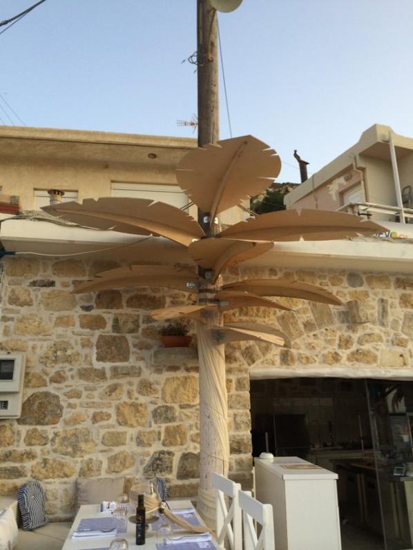 transformation d'un poteau electrique en palmier, devant un restaurant ( Gréce )