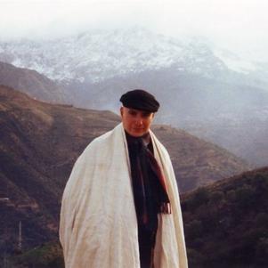moi avec mon burnous et derière mon village en Kabylie