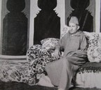 King Mohammed V posing in a saloon of his palace