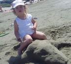 Eva a la plage sur un lezard en sable