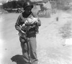 Un cameraman d'une Signal Photo Company, un bébé dans les br
