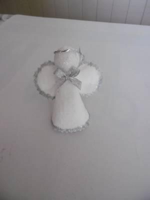 Un ange avec des cotons à démaquiller de forme ovale .