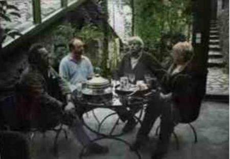 2003)  Jean reçoit des invités sous sa véranda