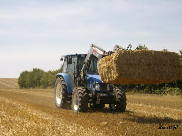 new holland TL90A suivi d'un plateau demarest
