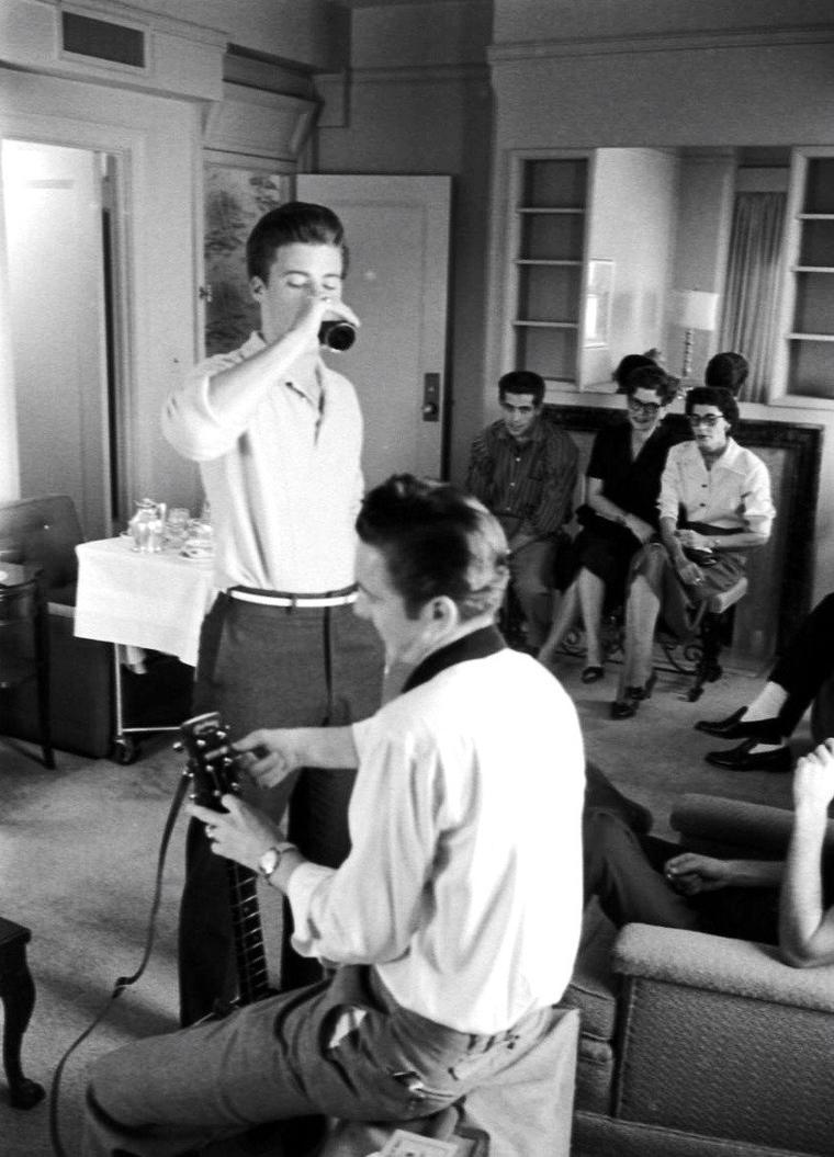 """Le jeune chanteur-acteur Ricky NELSON dans son avion ou dans sa loge, sous l'oeil de Ralph CRANE lors de son """"Thru Tulsa Tour""""."""