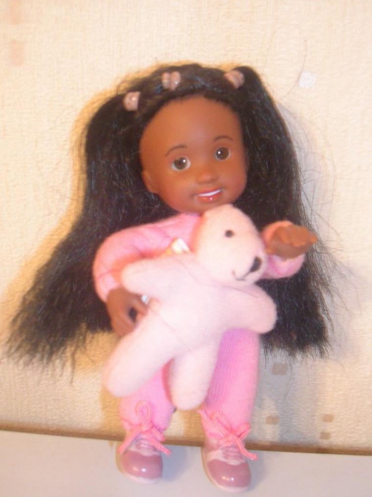 Jolie petite poupée brune avec des yeux marrons en verre