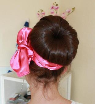 Chignon avec une grosse coque et un ruban rose