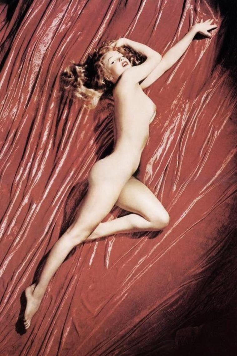 """27 Mai 1949 : NUDITE : Assisté par sa femme Natalie et son frère Bill, le photographe Tom KELLEY était considéré comme un créateur. Ses productions se distinguaient par la qualité de la lumière, l'originalité des images, plus une nouvelle approche des rapports entre le modèle humain et les différents produits qu'il présentait. N'étant plus sous contrat avec aucun des studios de cinéma, Marilyn avait besoin de 50 $ (soit pour payer sa chambre au """"Beverly Carlton Hotel"""" ou au """"Studio Club"""", soit pour récupérer sa voiture selon les versions). Marilyn débarqua au studio de Tom KELLEY, après avoir retrouvé dans ses affaires la carte de visite de celui-ci ; elle avait besoin d'argent, car elle n'avait aucune proposition à venir. Maquillée à outrance, elle portait un costume qui ne cachait rien de son anatomie : chemise blanche décolletée, jupe vermillon si moulante qu'elle entravait sa marche, et bien sûr, talons aiguille assortis. Elle n'évoquait pas vraiment l'idéal américain de la grande fille saine célébrée par les publicités en vogue, mais l'œil exercé de Tom KELLEY ne s'arrêta pas aux apparences ; oui, il avait un job pour elle. Il travaillait sur un projet de publicité pour une marque de bière et le modèle qu'il avait engagé venait de lui faire faux bond. Natalie KELLEY la conduisit dans un salon où elle retoucha son maquillage avant de lui tendre un maillot de bain une pièce et un ballon de plage multicolore. Deux semaines plus tard les fabricants de """"Pabst Beer"""" reçurent leur nouveau poster. Tom KELLEY la recontacta : la publicité pour la bière avait attiré l'attention de John BAUMGARTH, riche fabricant de calendriers de Chicago. Celui-ci avait contacté KELLEY : pour le prochain numéro du calendrier, il voulait le nouveau modèle, une photo artistique nue que Marilyn accepta. Elle signa un contrat avec Tom KELLEY sous le pseudonyme de Mona MONROE. La séance photos dura deux heures. Natalie, la femme de Tom KELLEY, y assista. KELLEY prit vingt-quatre photos : seule"""