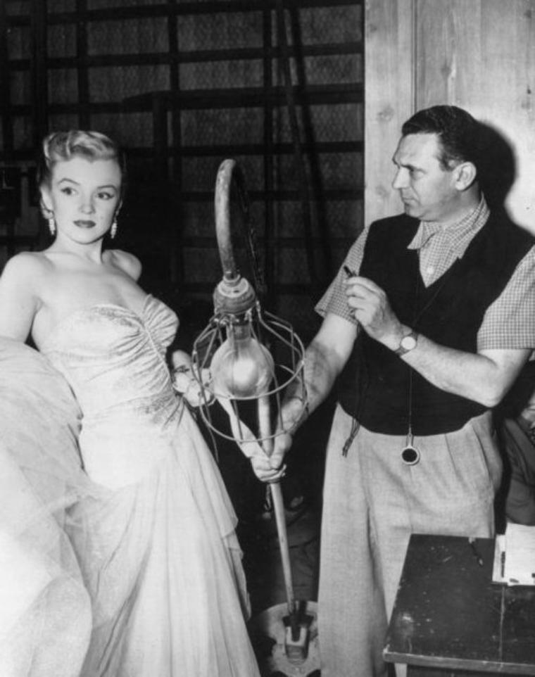 """1950 """"All about Eve"""" (part 2) : APPARITIONS de Marilyn dans le film ; apparition à la 43e minute au bras du critique DeWITT à une fête : elle est une starlette et rêve de se réaliser sur une scène de théâtre. Comme elle parle trop vite et sans réfléchir, vexant DeWITT, celui-ci l'envoie vers le producteur de théâtre Fabian, en n'oubliant pas de dénuder auparavant ses épaules... Toujours à la fête, plusieurs personnes sont assises dans l'escalier et discutent. Marilyn se fait servir un verre par Fabian. DeWITT lui adresse alors un commentaire (finalement autant pour Miss CASWELL que pour Marilyn) : « Well done. I can see your career rising in the east like the sun » (« Bien joué. Je vois ta carrière monter tel un soleil levant »). On apprend qu'elle a obtenu une audition. Quelques semaines plus tard : après l'audition, Marilyn a dû aller se remettre de ses émotions aux toilettes. À noter qu'elle porte dans cette scène le même pull-over que dans """"The Fireball"""" (1950) et """"Home Town Story"""" (1951)."""