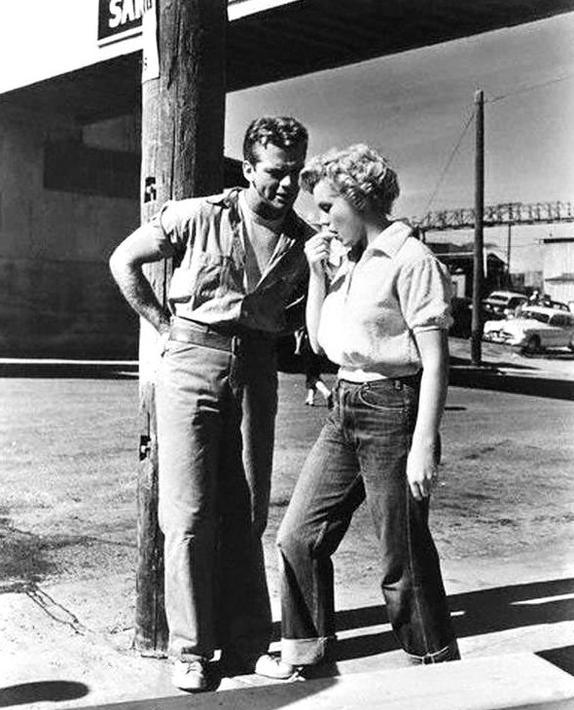 """1952, """"Clash by night"""" (Le démon s'éveille la nuit) ; Marilyn aux côtés de Keith ANDES l'un de ses partenaires dans le film. / CRITIQUE du film / Des mouettes se posent sur la mer tandis que les vagues qui s'abattent contre les rochers cernent quelques chalutiers amarrés à un port de pêche californien. Puis l'on suit les faits et gestes quotidiens de pêcheurs. C'est lorsque l'on s'attarde un instant sur un personnage − une jeune femme sort de son lit pour se rendre à son lieu de travail, l'usine de conserverie − que l'on reconnaît le visage encore juvénile mais radieux d'une Marilyn MONROE dans un rôle à contre-emploi. Décidément non, vous n'êtes pas en train de regarder un documentaire sur les chalutiers et les conserveries de ports de pêche américains. On a beau apercevoir Peggy/Marilyn affairée dans l'usine, au milieu de la chaîne humaine, sélectionnant mécaniquement les chairs des poissons morts, on devine bien que ces quelques plans d'ouverture sont ceux d'un maître. Fritz LANG filme l'Amérique mais se tient là où on ne l'attend pas..."""