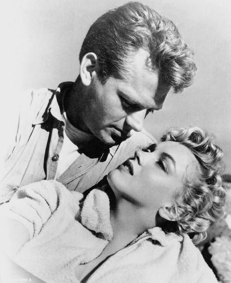 """1952, """"Clash by night"""" (Le démon s'éveille la nuit) (Marilyn et Keith ANDES, photos promotionnelles du film). / CRITIQUE / Au coeur d'un prologue documentaire sur la pêche en Californie (comme une incrustation néoréaliste), LANG n'a aucun scrupule à glisser un plan hétérogène : Marilyn, chemisette tendue à craquer et jeans XXL avec larges revers en bas, vision inédite de la working class en pressentiment fashion renversant. Hollywood transforme les usines de sardines en usines à rêves. Il y a autre chose dans ce plan. Une nostalgie anachronique. Filmant la sensualité solaire de Marilyn dans ces jeans hypersexy parce qu'à contre-emploi, LANG effleure un cinéma à venir, pour lequel il ne sera qu'un dinosaure. Il pressent la légèreté des années 60 et leur naïveté désirable. Le tournage fut pénible. Marilyn vomissait de trac et LANG s'exaspérait. A l'image, en jeune ouvrière prête à culbuter les préjugés, Marilyn apparaît comme un courant d'air, un contrepoint à ce mélo psychologique retors. Libre de ses mouvements et de ses pensées, elle incarne le futur, dont, bien sûr, LANG n'est pas dupe. Le mariage se refermera sur elle comme une trappe..."""