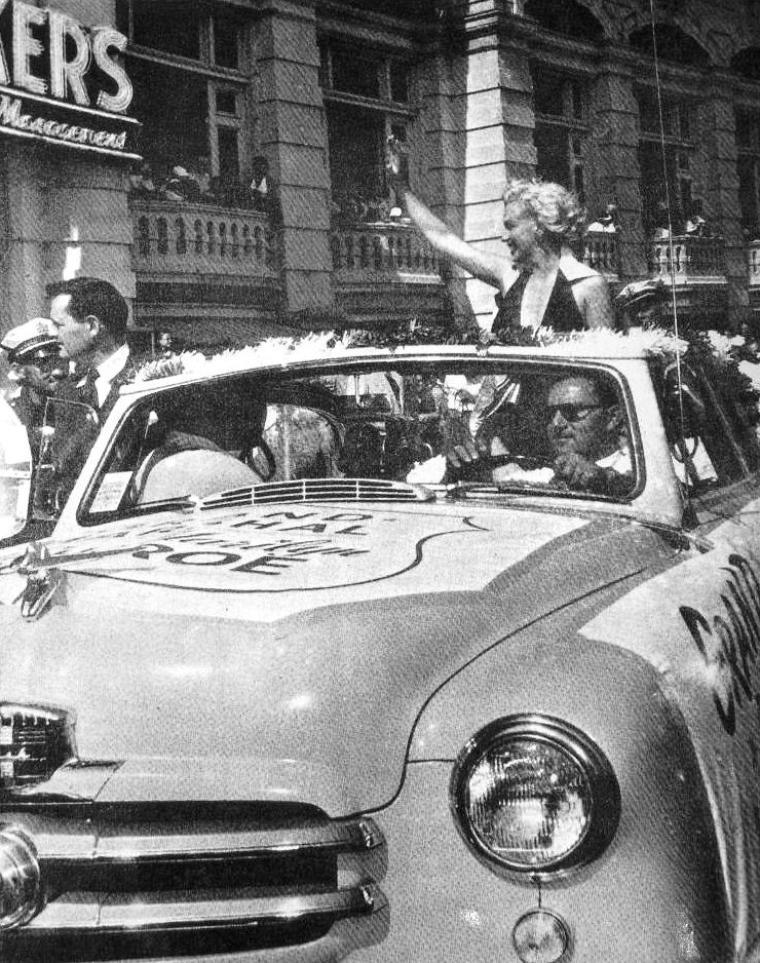 """1952 ATLANTIC-CITY : Il y a du monde en ce jour dans la ville pour l'élection de """"Miss America"""" ; les dirigeants de la FOX profitant de cette aubaine où toute la ville est de sortie pour un tel évènement, décident de faire parader Marilyn pour la promotion de son dernier film, """"Monkey business"""". Et c'est ainsi, qu'à bord d'une décapotable, Marilyn, les cheveux dans le vent se fait une joie de saluer les gens et de les remercier de mille baisers, les bras levés."""
