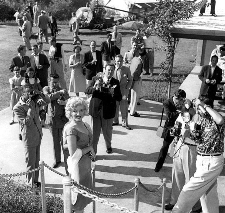 """On termine cette année 1952, qui fut riche en évènements et pour la notoriété montante de Marilyn grâce à son dernier film """"Niagara"""", avec la fête du musicien Ray ANTHONY (The Ray ANTHONY party) / La fête s'est tenue dans une villa de Sherman Oaks, dans le district de Los Angeles, situé dans la vallée de San Fernando. Marilyn, vêtue de la robe rouge du film """"Niagara"""", est arrivée en hélicoptère, puis s'est prêtée au jeu des photographes en faisant mine de jouer de la trompette et de la batterie sous les yeux avisés de Ray ANTHONY et de Mickey ROONEY, pendant que Ray ANTHONY chantait une chanson spécialement dédiée à Marilyn pour cette occasion, intitulée """"My Marilyn"""" . Parmi les nombreux convives, se trouvait aussi Sammy DAVIS Jr. Puis elle a rencontré le chien de la série """"Lassie"""". Les photographes présents: Bob WILLOUGHBY (qui a prit la plupart des photographies), Leni CARLSON et Phil STERN (part 5)."""