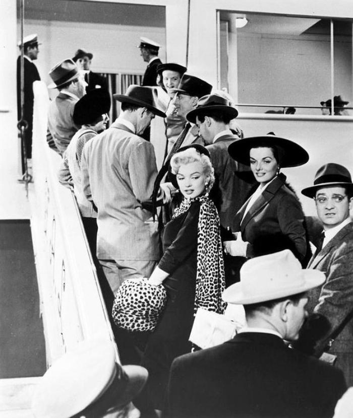 """1953 """"Gentlemen prefer blondes"""" (Les hommes préfèrent les blondes) de Howard HAWKS / CRITIQUE (part 3) / L'intrigue invraisemblable des """"Hommes préfèrent les blondes"""" tient en deux lignes : deux amies chanteuses et """"gâtées"""" par la nature embarquent pour Paris. L'une, Lorelei, est fiancée à un héritier. Le père de celui-ci la fait surveiller par un détective, car la jeune femme a tendance à succomber dès qu'elle voit des bijoux scintiller... """"Les hommes préfèrent les blondes"""" est au prime abord un pur divertissement hollywoodien, avec ce qu'il faut de burlesque (les bruits de dessin animé lorsque Lorelei embrasse son amoureux éperdu), de glamour (Marilyn et Jane RUSSELL en bombes sexuelles) et d'humour satirique, fin et rythmé par des rebondissements loufoques (Jane RUSSELL imitant Marilyn chantant """"Diamonds are a girl's best friend"""" dans une cour de justice, à moitié nue ! ). Mais HAWKS, qu'on ne pourrait accuser, bien qu'il s'y refusa, de ne pas être un """"auteur"""", n'a que faire d'une comédie ordinaire."""