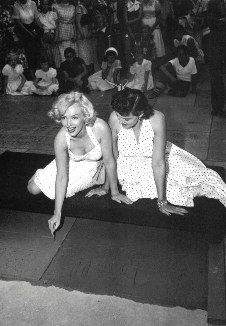 """Le 26 Juin 1953, Marilyn et Jane RUSSELL apposent leurs empreintes sur le trottoir, dans du ciment frais, du """"Grauman's Chinese Theatre"""" (part 2) / PRESENTATION / La salle, qui compte parmi les plus célèbres du monde, présente en avant-premières la plupart des grandes productions hollywoodiennes, dans des conditions de projection parfaites. Ses horaires d'ouverture vont de midi à minuit. À l'extérieur, devant ce bâtiment, les plus grandes stars du cinéma immortalisent leur passage en laissant leurs empreintes de pieds et de mains dans le ciment. À remarquer, celles de R2-D2 de """"Star Wars"""", de Donald DUCK, d'Humphrey BOGART, de Shirley TEMPLE et les minuscules talons de Marilyn MONROE. À l'origine, une vedette de cinéma en visite sur le chantier posa, par accident, son pied dans le ciment encore frais. Il n'en faut pas moins à Sid GRAUMAN, le fondateur des lieux, pour avoir l'idée de perpétuer la tradition. Chaque année, de nouvelles empreintes s'ajoutent à la collection."""