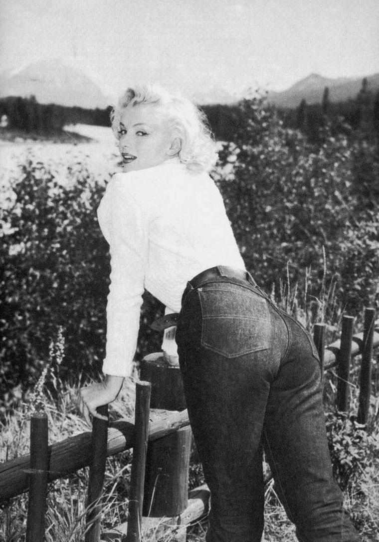 """1953, Marilyn pose en jean et pull face au Mont Kerkeslin et près de la rivière Athabasca au Canada lors du tournage du film """"River of no return"""" ; Marilyn séjourne à ce moment dans un des chalets (le n° 33) du """"Becker's Lodge Hôtel"""" à Jasper / ANECDOTE / Marilyn séjournera au """"Fairmont Banff Springs Hotel"""" (où l'on sert depuis un martini appelé """"Blonde Bombshell"""" en hommage à Marilyn), ainsi que dans les chalets du """"Becker's Lodge"""" (à cinq kilomètres au sud de Jasper)."""