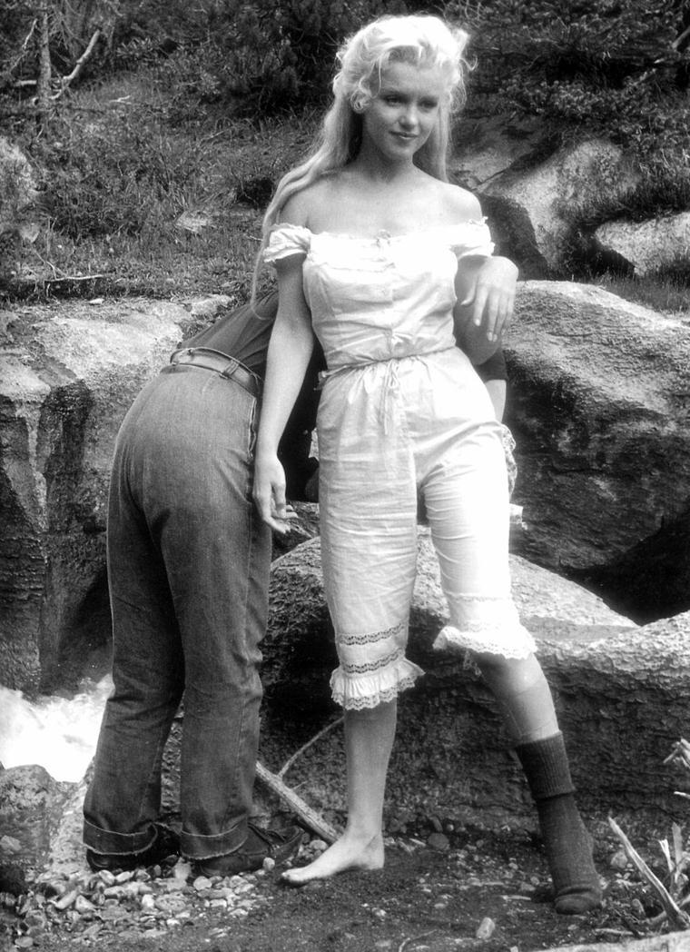 """""""River of no return"""" (La rivière sans retour) d'Otto PREMINGER / TENSION / L'hostilité régna sur le plateau lorsque le réalisateur Otto PREMINGER et Marilyn entamèrent une guerre d'usure. PREMINGER fit clairement comprendre qu'il travaillait sur ce film uniquement parce qu'il en était redevable par contrat à la Fox; Darryl ZANUCK lui fit miroiter la technologie du nouveau Cinémascope, et certains critiques notèrent que PREMINGER avait plus envie de filmer le paysage spectaculaire que d'arracher une interprétation dramatique à ses acteurs.  Comme  bon nombre de ses confrères il avait interdit au professeur d'art dramatique de Marilyn, Natasha LYTESS, l'accès au tournage, pour ne la rappeler que si le siège de la Fox le lui demandait comme une faveur.  Physiquement, ce fut un rôle très exigeant pour Marilyn, une grande part de l'action impliquant de faire tomber les protagonistes dans la rivière lors du franchissement de ses effrayants rapides.  Pour ses scènes, il fallut tremper Marilyn avec des seaux d'eau pour les raccords.  PREMINGER insista pour que ses vedettes fassent elles-mêmes leurs cascades, ce qui ne fut pas sans conséquences. Ainsi le radeau de Marilyn et de son partenaire Robert MITCHUM resta bloqué dans les rapides, et il fallut les secourir.  Dans ce film, Marilyn devait interpréter quatre chansons de Ken DARBY et Lionel NEWMAN, et elle répéta inlassablement « One silver dollar », « I'm gonna file my claim », « Down in the meadow » et la chanson-titre « River of no return », jusqu'à l'approcher de la perfection.  L'été où le film sortit, RCA vendit plus de 75 000 disques de « I'm gonna file my claim » en trois semaines seulement.  Les deux dernières semaines de tournage, Joe DiMAGGIO rejoignit Marilyn, notamment parce qu'elle avait été victime d'un accident : durant le tournage, elle était tombée du radeau dans l'Athabasca. Un médecin local diagnostiqua une possible entorse ; les médecins du studio ne virent là rien de sérieux, mais Marilyn insista pou"""