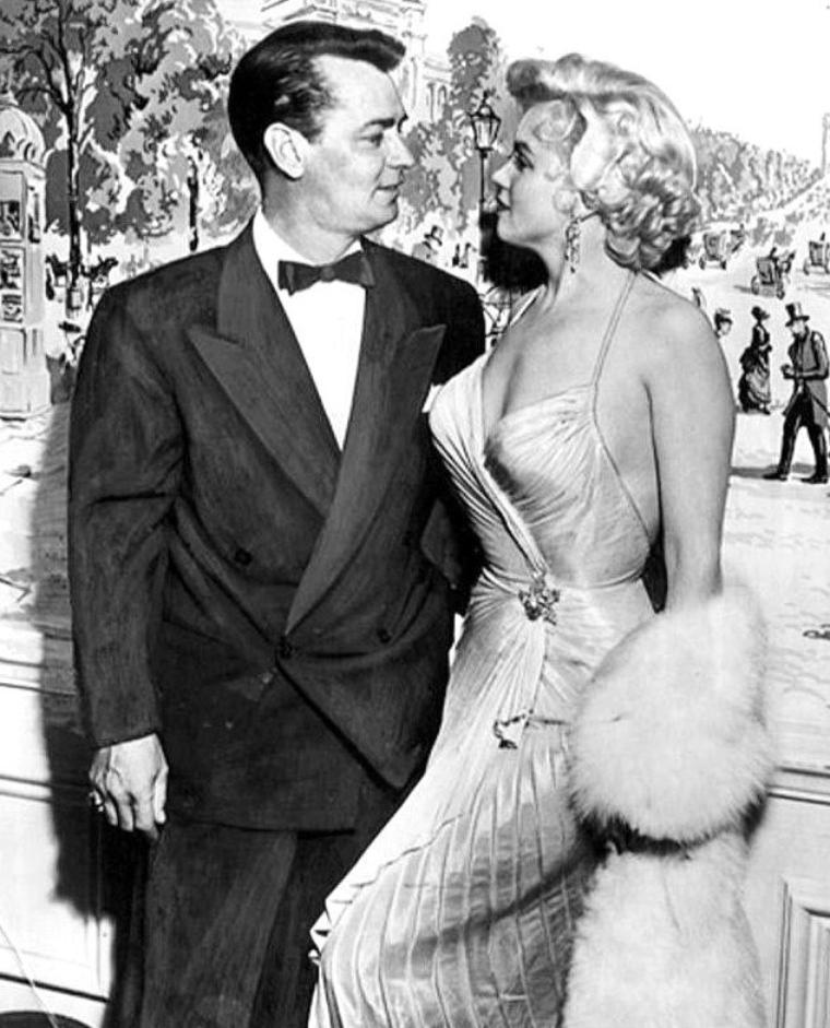 """1954, Marilyn accompagnée de son ami Sidney SKOLSKY reçoit le prix """"Photoplay Magazine Award"""" de """"The Most Popular Actress of 1953"""" (""""La meilleure actrice populaire de l'année 1953"""") pour ses rôles dans «Gentlemen prefer blonds» (""""Les Hommes préfèrent les blondes"""") et «How to marry a millionaire» (""""Comment épouser un millionaire""""). La remise de prix eut lieu dans une salle du Beverly Hills Hotel. De nombreuses stars participeront à la soirée, notamment l'acteur Alan LADD avec lequel Marilyn pose. / Marilyn porte la même robe qu'en 1953 lors d'un gala de bienfaisance avec Jack BENNY /"""