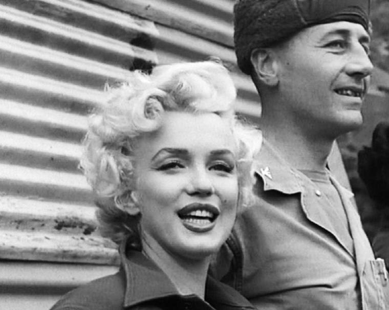 """Le froid et la pluie ne feront pas peur à Marilyn, qui portait une fine robe de cocktail à paillettes pour ses prestations scèniques. Elle racontera: """"Le sommet de ma vie fut de chanter là-bas pour les soldats. J'étais sur une scène en plein air. Il faisait froid, mais je vous jure que je ne m'étais jamais sentie aussi bien."""""""