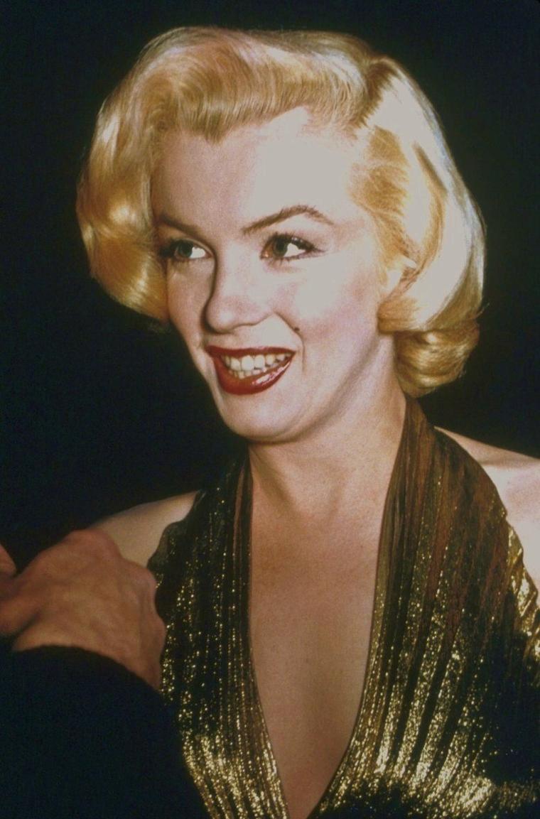 """1953 / Le magazine """"Photoplay"""" organisa la remise du prix de « L'étoile qui est montée le plus vite dans le ciel d'Hollywood en 1952 », en l'honneur de Marilyn. La réception eut lieu dans le """"Crystal Room"""" du """"Beverly Hills Hotel"""". Le maître de cérémonie était ce soir-là Jerry LEWIS. Marilyn était accompagnée de son ami le journaliste Sidney SKOLSKY. DiMAGGIO, voulant éviter les apparitions en public, était absent. Sa jalousie le poussera même à faire des apparitions surprises sur les tournages de Marilyn. Elle portait une robe en lamé or créée spécialement pour elle par William TRAVILLA  et qu'elle arborait dans « Gentlemen prefer blondes ». Elle fut le point de mire quand elle fit son entrée, vêtue de cette robe « qui  donnait l'impression d'avoir été peinte sur elle », comme le rapporta le lendemain la journaliste Florabel MUIR dans son article « Florabel Muir reporting » du 10 février paru dans le """"Los Angeles Mirror"""". « Il suffit d'un mouvement du derrière pour que Marilyn MONROE vole la vedette…Tous les invités se mirent à l'applaudir (tandis que) deux autres stars du cinéma, Joan CRAWFORD et Lana TURNER, étaient à peine regardées. A côté de Marilyn, toutes les autres paraissaient bien ternes »."""