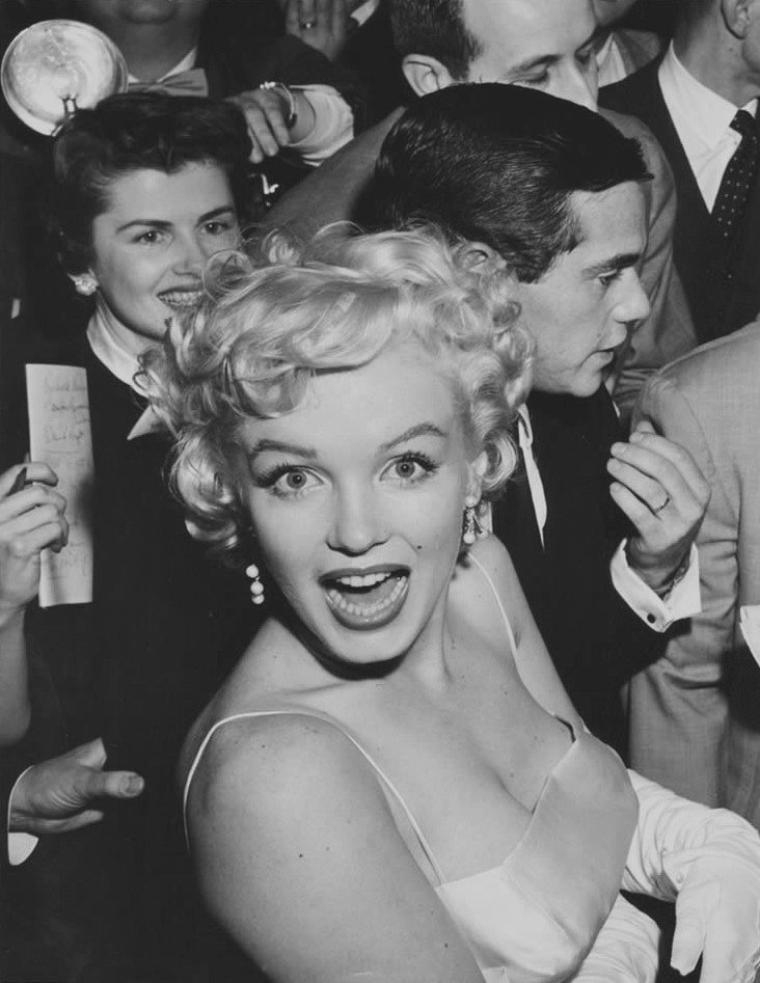 """1955 / Le 7 janvier 1955, Marilyn organise avec désormais son associé, le photographe Milton H. GREENE, une conférence de presse où sont conviés près de quatre-vingt journalistes, ainsi que quelques amis. La réunion a lieu dans la maison de leur avocat Frank DELANEY, sur la 64ème Avenue à New York.  Marilyn portait une robe de satin blanc et un manteau de fourrure d'hermine, des créations du couturier Norman NORELL. Elle portait des boucles d'oreilles en diamants de chez """"Van Cleef & Arpels"""". Elle annonça elle-même officiellement la création de la maison de production """"Marilyn MONROE Productions"""", dont elle en était la présidente (elle détenait 51% des parts), et Milton GREENE le vice-président (il en détenait 49%). Frank DELANEY répondit à quelques questions des journalistes, déclarant notamment qu'elle n'était plus sous contrat avec la Fox et qu'elle envisageait de travailler pour la télévision. De leur côté, la Fox tiendra aussi une conférence de presse pour affirmer que Marilyn était encore sous contrat pour quatre ans. Marilyn ne s'était pas montrée en public depuis près d'un mois, ce qui attisait la curiosité des journalistes mais aussi de ses fans, dont certains furent conviés. Parmi les convives célèbres, figuraient la journaliste à potins Elsa MAXWELL, le dramaturge Sidney KINGSLEY, le compositeur Richard RODGERS (ami de Milton GREENE), le photographe Sam SHAW, ainsi que Marlène DIETRICH. Après la conférence de presse, Marilyn, Milton et Marlène fêtèrent l'événement au """"Copacabana Club"""", où se produisait Frank SINATRA. Ils allèrent ensuite dîner avec SINATRA au """"Club 21"""" et finirent la soirée chez Marlène DIETRICH."""
