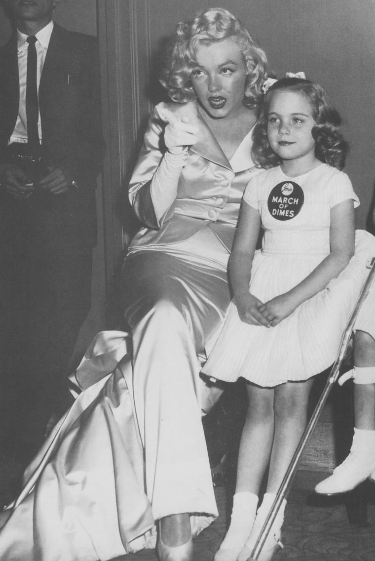 """1958 / Marilyn participe au show de mode annuel """"March of Dimes"""", qui se déroulait au """"Waldrof-Astoria"""" de New York le 28 janvier 1958, accompagnant les jumelles de 6 ans Lindy et Sandy Sue SALOMON. Les bénéfices de ce show sont reversés à la recherche de vaccination de la polio. Marilyn porte un ensemble veste et jupe longue de couleur champagne en soie et satin, et dont la veste fut conçue par John MOORE pour """"Talmack"""". Les participants au show étaient composés des membres du groupe de haute-couture de l'institut """"New York Gress"""", ainsi que de designers new-yorkais, californiens et italiens."""