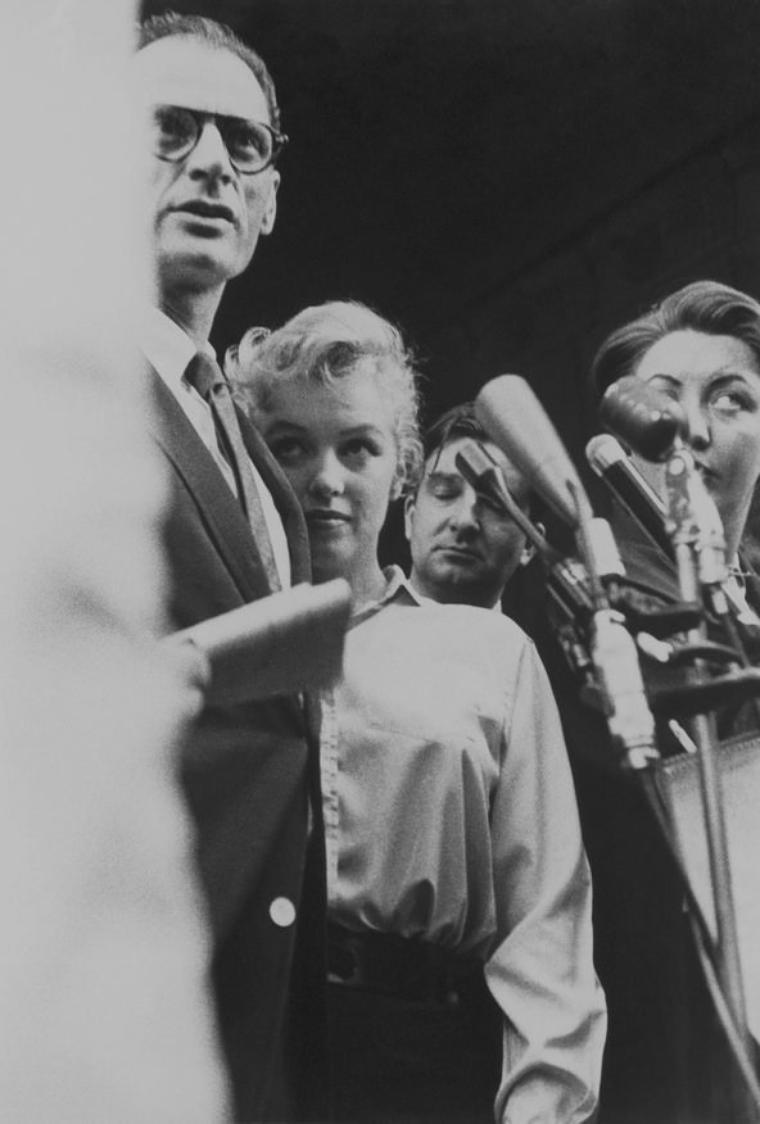 """1956 / Devant le """"Sutton Palace"""", où ils résident, Marilyn annonce devant quelques dizaines de journalistes qu'elle va épouser le dramaturge Arthur MILLER, à la surprise générale, le 29 juin. La plus belle fille de Hollywood, la tornade peroxydée, dans les bras d'un des cerveaux les plus affûtés des Etats-Unis, c'était une « story » impensable même pour le plus allumé des scénaristes. MILLER, qui venait de divorcer de sa première femme Mary SLATTERY, avait remporté le prix """"Pulitzer"""" pour « Mort d'un commis voyageur » en 1949. Sa pièce « Les sorcières de Salem » sera jouée sans interruption pendant dix ans."""