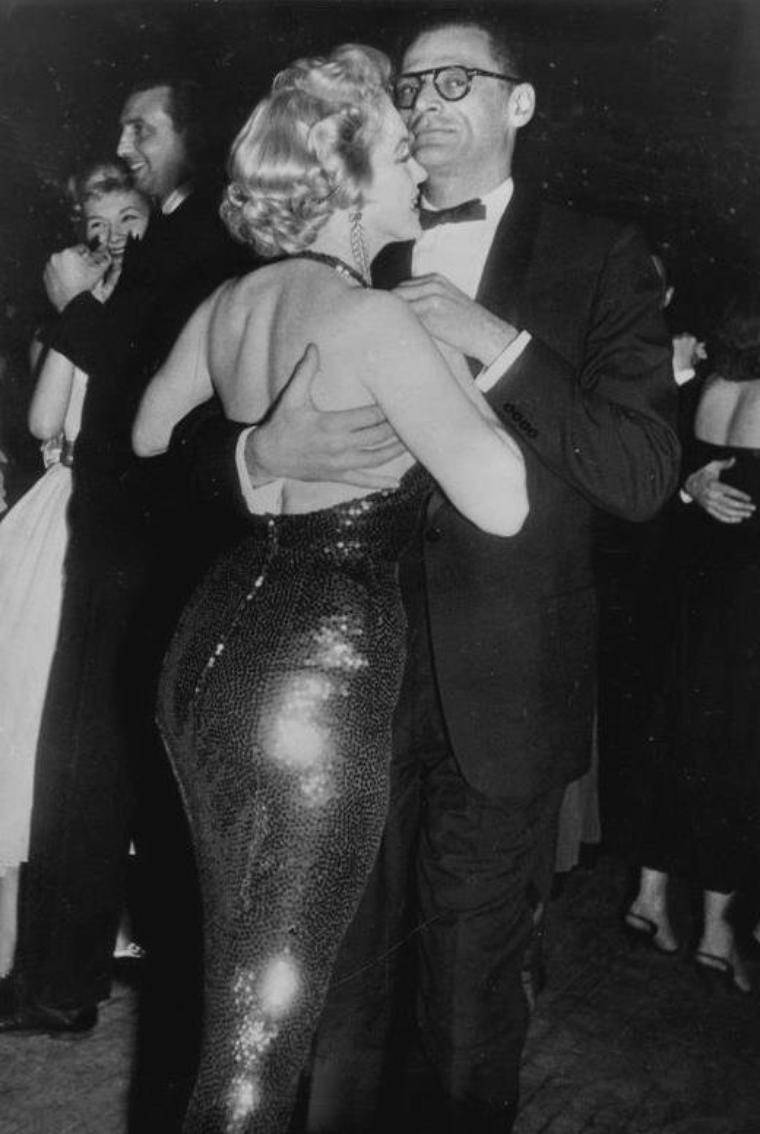 """1956 / Marilyn et Arthur sont conviés à la Première du film """"Baby-doll"""" au """"Victoria Theater"""", à Broadway, N.Y. ; Marilyn participera même à une émission de radio ce soir là. (petite anecdote pour FANS AVERTIS) / C'est la première fois que Marilyn portera sa fameuse mèche de cheveux sur le côté gauche, les photos n'étant pas tirées à l'envers, comme sur certaines, que je m'efforce souvent de rectifier et la seconde fois fut en 1961, au """"Crescendo-club"""", voir article ci-après). Marilyn, porte toujours la mèche de cheveux du côté droit, et la mouche est toujours située sur la joue gauche."""