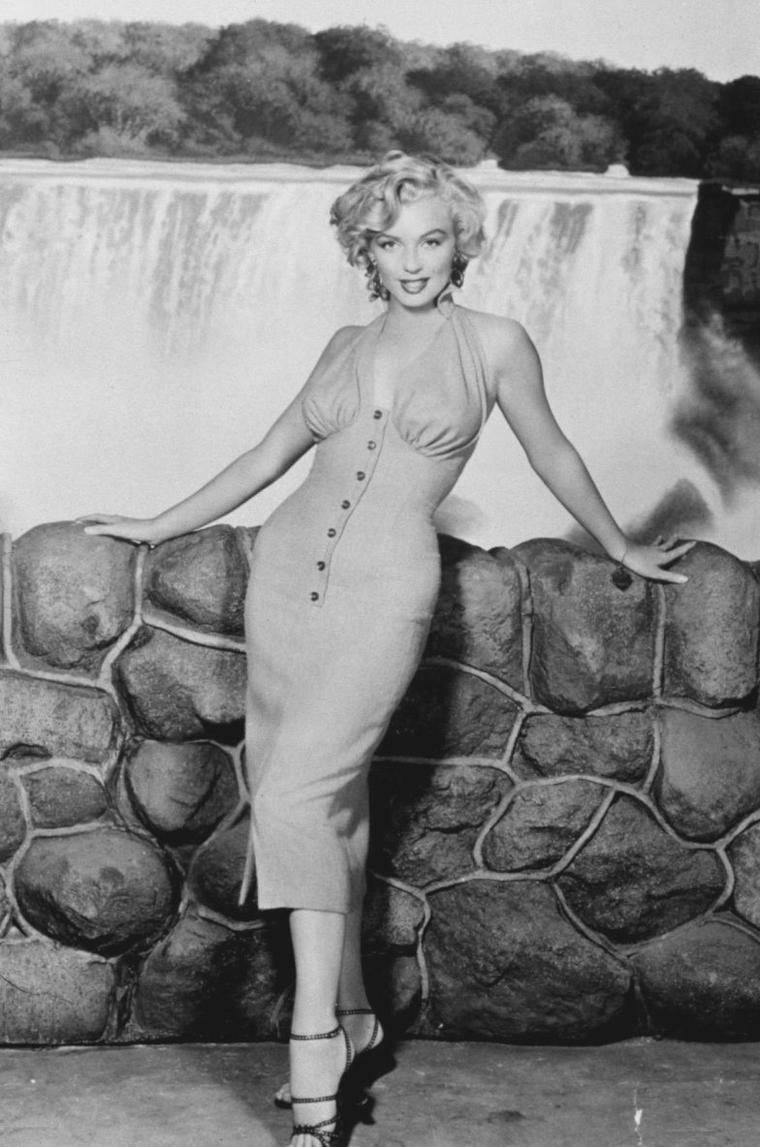 "1952 / Marilyn posant dans sa robe rouge à boutons lors du tournage de ""Niagara""."