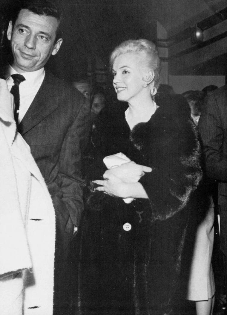 """1960 / L'idylle... Il fut très vite évident pour tout le monde, sur le plateau du """"Milliardaire"""", que les deux vedettes prenaient le titre original du film, """"Let's Make Love"""", au pied de la lettre. L'idylle qui venait de naître entre Marilyn et Yves MONTAND fit la une des potins d'Hollywood. L'échotière Dorothy KILGALLEN fut la première à alerter le public en écrivant : « Une actrice lauréate d'un Oscar cette année a actuellement des problèmes conjugaux. » Une femme de chambre de l'Hôtel """"Beverly Hills"""" lâcha quelques indiscrétions bien épicées au journaliste James BACON, et plus personne n'ignora l'affaire. C'était du pain bénit pour la presse spécialisée. On racontait que la star s'était présentée « nue sous son vison » à la porte du bungalow 20 ; que Arthur MILLER, retournant chez lui pour prendre la pipe qu'il y avait oubliée, avait surpris les deux amants au lit... Hedda HOPPER, la redoutée commère, y alla de son conseil d'amie dans les dizaines de journaux qui publiaient sa chronique : « Il vous reste encore à prouver que vous êtes une grande comédienne. Votre succès n'est dû qu'à la publicité. Je vous en conjure, Marilyn, cessez de vous autodétruire » Quand Arthur MILLER revint à Hollywood pour rejoindre Marilyn à l'Hôtel """"Beverly Hills"""", la nouvelle était partout. « Je n'y pouvais rien, racontera plus tard Arthur. À cette époque, mon nom était devenu pour elle synonyme de trahison et de confiance perdue. Et il n'y avait aucun espoir de la faire changer d'avis. C'était ainsi. » Si on en croit Norman ROSTEN, « MONTAND ne fut pas le seul. Il y en avait eu d'autres. Elle n'était plus depuis un certain temps d'une fidélité irréprochable à Arthur. Marilyn avait terriblement besoin de cela. Quand elle perdait confiance, elle allait vers d'autres hommes pour avoir quelque chose à quoi se raccrocher ». Les dernières prises de vues du """"Milliardaire"""" avaient été repoussées à la mi-juin, et Marilyn voulait croire que ce qu'elle vivait avec Yves MONTAND n'était pas une a"""