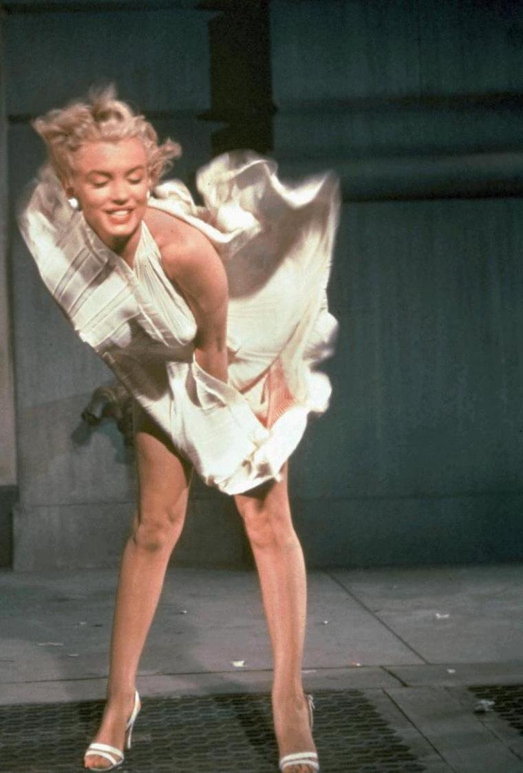 """1954 / SCENE MYTHIQUE / On dressa des barrières devant le """"Trans-Lux Theater"""", au coin de Lexington Avenue et de 52nd Street. Vers une heure du matin, alors que le tournage devait débuter, plusieurs centaines de photographes se bousculaient pour prendre place, au milieu d'une foule de 5000 spectateurs au bas mot (selon l'estimation de Billy WILDER, mais un journal avança le nombre d'un millier environ), qui poussaient des hourras chaque fois (il y eut quinze prises) que la jupe de Marilyn s'envolait : sous l'effet du courant d'air provoqué par un énorme ventilateur installé en dessous d'une grille de métro, la robe dévoilait ses jambes et sa culotte blanche. Le tournage de cette scène (devenue mythique) eut un certain nombre de conséquences. Tout d'abord aucune des prises ne fut utilisable : il y avait trop de bruit, pas assez de liberté de mouvement à cause de la foule, et le ventilateur utilisé ne produisait pas l'effet désiré. Dans la scène définitive, tournée en studio, à la Fox, Marilyn marche sur une grille, sa jupe se soulève juste au-dessus de ses genoux, et un raccord montre son visage où s'exprime le plaisir d'une brise rafraîchissante par une chaude nuit d'été. Ce n'est là qu'un chaste reflet des photos osées que prirent les hordes de photographes cette nuit-là sur Lexington Avenue, et pourtant il fallut couper l'un des trois plans de la séquence originale  pour satisfaire au « code Hays » définissant strictement ce qui est convenable à l'écran. La scène de la jupe qui s'envole, peut-être la plus célèbre de la carrière de Marilyn, est l'archétype du glamour des années 1950, et c'est la raison pour laquelle elle apparut sous une forme ou une autre dans de nombreux films, des années durant, comme « Tommy » (1975), « Une nuit de réflexion » (1985) et « Pulp fiction » (1994)."""