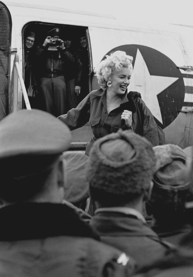 """1954 / Arrivée de Marilyn en Corée / En février 1954, Marilyn arrive en Corée. Il fait un froid polaire, la guerre est dure pour les G.I.'s et les conditions sont terribles. Mais Marilyn, qui vient d'interrompre son voyage de noces pour aller chanter en Corée - son mari Joe DiMAGGIO est resté au Japon pour le démarrage de la saison de base-ball - n'en a cure. Elle sent que le public l'adore. Et c'est vrai : en quatre jours, elle donne 10 shows, parfois face à un public de 17 000 spectateurs. """"Debout, sous la neige, face aux soldats, j'ai senti, pour la première fois de ma vie, que je n'avais peur de rien. J'étais heureuse"""", avouera-t-elle plus tard.  Heureuse ? Voire. Car Marilyn s'exhibe en robe décolletée, et ne porte pas de sous-vêtements. Les bidasses sont ravis, et, parfois, des émeutes se déclenchent, dont la star s'extrait en hélicoptère. En revanche, Joe DiMAGGIO, qui regarde les actualités à la télé, est furieux. Il voit son épouse chanter """"Diamonds Are A Girl's Best Friend"""", """"Bye Bye Baby"""", """"Somebody Loves Me"""" et """"Do It again"""" (que la censure militaire a modifié en """"Kiss Me again"""", moins provocant), et il fulmine. Immense vedette, absolument adoré aux Etats-Unis, DiMAGGIO est d'une jalousie féroce, jalousie qui provoquera la fin d'un mariage ayant duré neuf mois."""