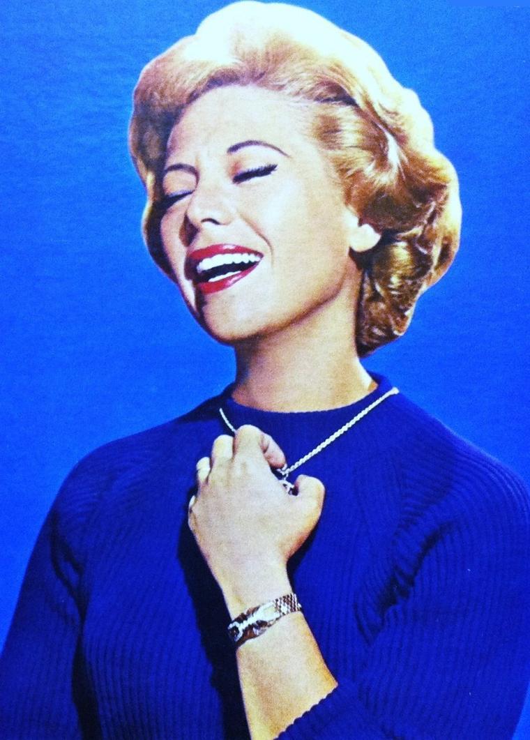 """Artiste complète / Dinah SHORE a joué dans une dizaine de films et séries T.V., fervente supportrice du développement du golf au féminin, artiste peintre et chanteuse avec au palmarès le titre """"I'll Walk Alone"""" qui fut n°1 aux États-Unis pendant 4 semaines en octobre et novembre 1944, et """"Buttons and Bows"""" durant 10 semaines entre octobre 1948 et janvier 1949."""