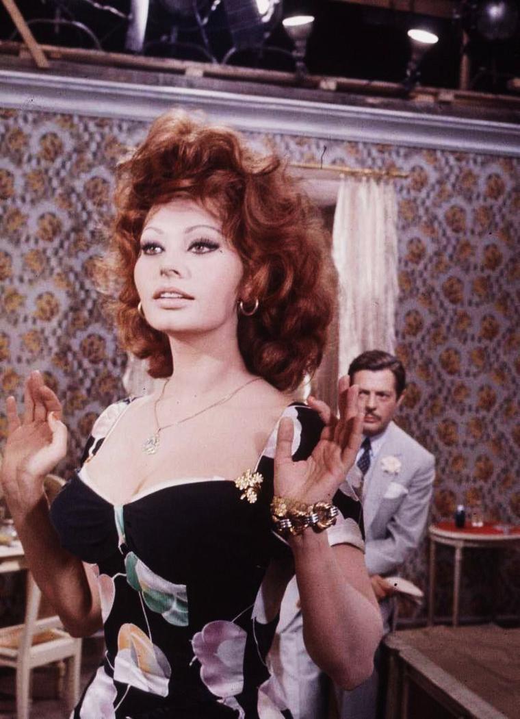 """ON THE SET / Sophia LOREN et Marcello MASTROIANNI sur le tournage du film """"Mariage à l'italienne"""" (titre original : """"Matrimonio all'italiana"""") est un film italien réalisé par Vittorio De SICA, sorti en 1964. / SYNOPSIS / Domenico SORIANO, un riche séducteur napolitain, a rencontré une prostituée, Filumena MARTURANO, qu'il a lui-même enlevée à la rue et invitée à partager sa vie. Mais Filumena se trouve désormais réduite au rôle de bonne pour la mère de Domenico. Un jour, malade et sur le point de mourir, Filumena demande à Domenico de l'épouser en urgence. Y voyant une bonne occasion de soulager sa conscience, Domenico accepte le mariage, au chevet de Filumena. Cependant, une fois le mariage prononcé, la mariée se lève subitement de son lit, révélant ainsi son stratagème pour assurer sa stabilité économique et garantir un avenir à ses trois enfants, dont elle avait toujours caché l'existence à Domenico. Elle lui avoue même que l'un d'entre eux est son fils, mais ne lui précise pas duquel il s'agit, de peur qu'il n'assume sa responsabilité de père qu'avec lui. Après avoir inutilement cherché lequel de ces enfants était son fils, et après de nombreuses menaces envers Filumena, Domenico accepte enfin les trois enfants comme les siens, permettant ainsi à sa femme d'être heureuse. Sous la forme d'un fil continu de flashback sur les vingt dernières années des personnages, le film nous présente les rapports complexes liant ces deux amants."""