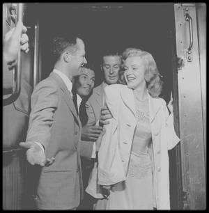 """1949 / Marilyn est en voyage à travers les Etats-Unis pour promouvoir le film """"Love Happy"""". Elle se rend à New York, chargée par le magazine """"Photoplay"""" de participer à la remise du concours """"Dream Home"""" (""""Maison de Rêve"""") organisé par le magazine. Marilyn est accompagnée des acteurs Don DEFORE et Lon McALLISTER qui la suivirent dans le train et lors de la remise du prix qui se déroule à Warrensburg, New York. Marilyn, ayant entendue dire qu'à New York il faisait toujours beaucoup plus froid qu'à Los Angeles, était vêtue d'une robe en laine noire, alors qu'il faisait une chaleur accablante et ce, dès le trajet en train. Sur place, Lester COWAN lui acheta une robe blanche en coton, achetée chez un grossiste à New York, qu'elle porta tout le reste du séjour. Elle remet les clés à la gagnante, Virginia McALLISTER, accompagnée de son petit garçon. Puis elle visite la maison qui contient tout l'équipement moderne de l'époque. Les photos de l'événement paraîtront dans l'édition de Novembre 1949 du magazine """"Photoplay""""."""