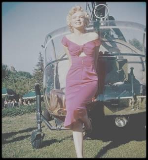 """1952 / C'est en hélicoptère, selon la légende (car Marilyn arrive en fait en voiture) que Marilyn, invitée d'honneur, se présente à la fête du chef d'orchestre Ray ANTHONY, faisant sensation dans sa robe fushia qu'elle porte dans le film qu'elle tourne alors, """"Niagara"""" de Henry HATHAWAY. (la plupart des photos sont signées Bob WILLOUGHBY)."""