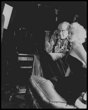 1952 / Marilyn écoutant les conseils du photographe Frank POWOLNY pour une session photos.