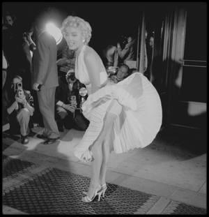 """15 Septembre 1954 / TOURNAGE DE LA SCENE CULTE du film """"The seven year itch"""" :  Walter WINCHELL persuada Joe de se joindre à la foule de plusieurs centaines de curieux qui attendaient pendant des heures, devant le """"Trans-Lux Theater"""", sur Lexington Avenue au coin de la 52nd Street, pour voir enfin la jupe plissée de Marilyn s'envoler, en dévoilant ses jambes, au dessus d'une bouche de métro. La scène fut tournée vers une heure du matin, au milieu d'une foule qui poussait des hourras chaque fois que la jupe de Marilyn s'envolait, sous l'effet du courant d'air provoqué par un énorme  ventilateur installé en dessous d'une grille de métro. Il y eut quinze prises et le tournage dura cinq heures. Le tournage de cette scène était essentiellement publicitaire : en effet tout le monde savait qu'elle serait de toute façon tournée au studio de la Fox car les bruits ambiants couvraient complètement les dialogues, il n'y avait pas assez de liberté de mouvement à cause de la foule et le ventilateur utilisé ne produisait pas l'effet désiré. (quelques photos signées Elliott ERWITT)."""