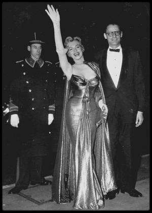 """29 Octobre 1956 / Marilyn, accompagnée d'Arthur MILLER et de Milton GREENE, fut présentée à la reine d'Angleterre, Elizabeth II, à """"l'Empire Theatre"""", à Leicester Square. Avant une projection du film britannique « The battle of the river plate », vingt vedettes de cinéma furent présentées à la reine, dont Brigitte BARDOT, Joan CRAWFORD, Anita EKBERG, Victor MATURE ou encore Anthony QUAYLE... Elle sera immortalisée peu après au musée de cire de Mme TUSSAUD."""