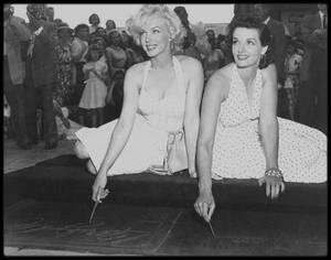 """26 Juin 1953 / Suite à la sortie du film """"Gentlemen prefer blondes"""" et du succès auprès du public de ce dernier, Marilyn et Jane RUSSELL sont invitées à poser leurs empreintes devant le """"Grauman's Chinese Theater"""" d'Hollywood, devant une foule immense et un parterre de journalistes ; l'anecdote veut que Marilyn voulait apposer sur le i de son prénom un vrai diamant, elle se ravisa pour y faire mettre un cristal, ce dernier sera volé quelques temps après la cérémonie."""