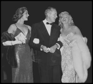 """4 Novembre 1953 / Marilyn se rendit à la première du film """"How To Marry a Millionaire"""" (""""Comment épouser un millionnaire"""") dans lequel elle tient le rôle de Pola DEBEVOISE. Accompagnée de Lauren BACALL (sa partenaire dans le film), Humphrey BOGART et Nunally JOHNSON (producteur et scénariste), Marilyn fit une arrivée remarquée au """"Fox-Wilshire Theater"""" dans une sublime robe blanche qui avait dû être cousue sur elle. Earl LEAF, photographe, chroniqueur, et ami de Marilyn, décrivit son apparition ce soir là : """"Marilyn était l'incarnation vivante d'un rêve de petite fille... Des personnes du studio la dirigèrent vers les micros. Humphrey BOGART avait passé tout l'après-midi à la coacher pour savoir quoi dire à la foule. """"Dis leur que tu es venue pour voir comment tu as gâché ce film"""", il pensait que cela ferait un bon gag. Au lieu de ça, une impulsion d'une belle simplicité s'empara d'elle et dit, """"Je suis tellement ravie d'être à ma première grande première que je pourrais presque en pleurer !""""."""