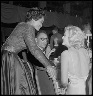 """13 Juin 1957 / Marilyn et Arthur se rendent à la Première du film « The Prince and the showgirl » au """"Radio City Music Hall"""" à New York. Jack WARNER était présent ce soir là. Marilyn revit Amy GREENE, enceinte de son deuxième enfant. Cela faisait plusieurs mois qu'elles ne s'étaient pas vues. Une fête fut ensuite donnée au """"Waldorf Astoria"""". Les critiques firent un accueil plutôt mitigé au film, mais reconnurent que c'était là une des meilleures interprétations de Marilyn, qui volait aisément la vedette à Laurence OLIVIER. C'était aussi le premier film pour lequel son statut de partie contractante indépendante lui donnait droit à un pourcentage sur les bénéfices, forme de rémunération très inhabituelle à l'époque de la toute puissance des studios ; elle toucha 10% des bénéfices (160 000 $ ; le film ayant généré une recette de 1.6 millions de $)."""