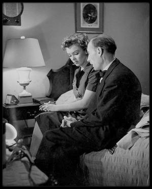 """1952 / Marilyn, notamment avec Roy Ward BAKER ou Richard WIDMARK, lors du tournage du film """"Don't bother to knock"""". Après avoir prêté Marilyn à d'autres studios, la Fox donna à son nouveau sex-symbol son premier grand rôle dans un film. Immédiatement après avoir interprété une employée de pêcherie dans « Clash by night » (1952), Marilyn incarna une baby-sitter à l'esprit dérangé et dangereusement névrosée : deux rôles singulièrement éloignés de celui de blonde explosive qu'elle tenait dans ses quatorze films précédents.  « Don't bother to knock » était tiré d'une histoire à suspense de Charlotte ARMSTRONG, « Mischief », publiée à l'origine dans le magazine """"Good housekeeping"""". Son jeu fut diversement apprécié, mais en règle générale, les avis furent favorables. Des années plus tard, Marilyn considérait qu'il s'agissait là d'une de ses meilleures interprétations.  Le rôle de Nell FORBES fut probablement une épreuve émotionnelle importante. On peut penser que Marilyn fit appel à sa propre enfance malheureuse et aux visites à sa mère dans les institutions psychiatriques pour comprendre la solitude de son personnage, ainsi que les conséquences d'années d'internement. De sa propre vie elle pouvait s'inspirer pour l'attrait qu'exerce une vie fantasque et pour les blessures qui peuvent mener au suicide.  Le budget du film était limité, ce qui contraignit le réalisateur anglais, Roy BAKER, à se contenter des premières prises. Compte tenu du trac considérable dont souffrait Marilyn, le résultat est impressionnant.  Natasha LYTESS, dont Marilyn avait exigé la présence sur le plateau, raconta : « Je n'avais pas grand chose à faire. Elle était terrifiée par le film mais connaissait exactement les exigences du rôle et la façon dont elle devait jouer. J'essayais simplement de lui donner confiance. ».  Le pilote Jed TOWERS, interprété par Richard WIDMARK, définit très bien le personnage : « Tu es une nana très changeante...de la soie côté pile, du papier de verre côté face. »."""