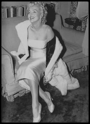 """7 Janvier 1955 / Milton GREENE réunit une conférence de presse avec quatre-vingt journalistes, quelques amis et  plusieurs partenaires potentiels chez Frank DELANEY, un de ses avocats (les avocats Frank DELANEY, Irving STEIN et Lloyd WRIGHT travaillèrent avec Milton GREENE à la création des """"Marilyn MONROE Productions""""), sur la 64ème rue. Marilyn n'avait pas été vue en public depuis plus de trois semaines, et la curiosité des journalistes était à son comble. Les journalistes Dorothy KILGALLEN et Walter WINCHELL, hostiles à Marilyn, furent les seuls absents. Elle annonça elle-même officiellement la création de la maison de production """"Marilyn MONROE Productions"""", dont elle était présidente avec 51 % du capital, et Milton GREENE le vice-président avec 49 % du capital. Lorsqu'on lui demanda comment elle entend concilier cela avec la Fox, DELANEY répondit qu'elle n'était plus sous contrat avec la Fox et qu'elle envisageait de travailler pour la télévision. La Fox convoquera une conférence de presse et annoncera que Marilyn était bel et bien encore sous contrat avec le studio et qu'elle leur devait encore quatre ans. A la réception qui suivit l'annonce de la création de sa maison de production, elle était vêtue d'une robe de satin blanc et d'un manteau d'hermine (crées par le couturier Norman NORELL) et portait des boucles d'oreilles de chez """"Van Cleef & Arpels"""", les  premiers véritables diamants qu'elle porta. A cette soirée assistèrent entre autres Elsa MAXWELL, le dramaturge Sidney KINGSLEY, le  compositeur Richard RODGERS (ami de Milton GREENE), Janet LEIGH et Tony CURTIS, et Marlène DIETRICH, qui proposa à Marilyn de passer chez elle, sur Park Avenue, plus tard dans la soirée, pour prendre un verre. Marilyn fêta l'événement le soir, avec les GREENE au """"Copacabana Club"""", un night-club où se produisait Frank SINATRA. Celui-ci les emmena dîner au « Club  21 ». Ils passèrent ensuite chez Marlène DIETRICH. Frank DELANEY, en annonçant que Marilyn n'était plus sous contrat"""