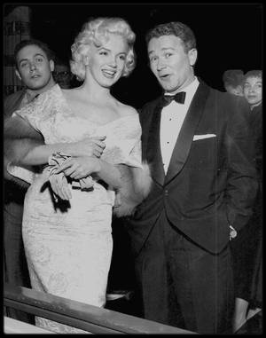 """9 Mars 1955 / Marilyn au bras de Milton GREENE se rend à la Première de « East of Eden », au """"Astor Theater"""" de New York ; elle se porta volontaire  pour servir d'ouvreuse. A cette soirée furent présents, entre autre, son agent new-yorkais de la MCA  Jay KANTER, Milton GREENE, Sammy DAVIS Jr, le journaliste Earl WILSON, l'acteur Richard DAVALOS et l'animateur Milton BERLE. La soirée était organisée au profit de """"l'Actors Studio"""", qui avait désespérément besoin d'un lieu à lui. Cette collecte devait servir à acheter une ancienne église grecque. Après la projection, elle se rendit à une réception durant laquelle les membres du Studio et ses partisans voulaient tous rencontrer la plus récente adepte de STRASBERG. Au cours de cette soirée, Marilyn rencontra Arthur MILLER accompagné de sa s½ur, la comédienne Joan MILLER COPELAND. C'est MILLER qui l'aborda et ils parlèrent un moment. Quinze jours plus tard, MILLER appela Paula STRASBERG pour lui demander le numéro de téléphone de Marilyn. Ils se revirent plus tard, à partir du printemps, chez les ROSTEN, et leur liaison commença."""