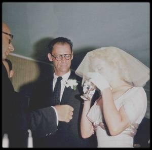 1er Juillet 1956 / Photos Milton GREENE ; Ce matin là, Marilyn se convertit au judaïsme (22ème Tammouz 5716 du calendrier juif). Son certificat de conversion fut signé par Milton GREENE, Arthur MILLER, Kermit MILLER (son frère) et le rabbin Robert GOLDBERG. Le mariage religieux d'Arthur MILLER et Marilyn fut ensuite célébré par le rabbin GOLDBERG, chez l'agent littéraire de MILLER, Kay  BROWN, à South Salem (Etat de New York), assisté de Kermit MILLER et d'Hedda ROSTEN. Ses dames d'honneur furent Amy GREENE (qui l'aida à s'habiller et à se maquiller), Hedda ROSTEN et Judy KANTOR. Sa robe de mariée en mousseline beige avait été dessinée par les couturiers John MOORE et Norman NORELL. Ce fut Milton GREENE qui l'accompagna pour sortir et la confia au bras de Lee STRASBERG (expression ultime de son rôle de père vis-à-vis de Marilyn) qui la mena à l'autel, sous le dais nuptial. Selon le rite juif, les mariés burent du vin, échangèrent les alliances et MILLER cassa son verre en souvenir de la destruction de Jérusalem. Au cours des deux derniers jours, MILLER avait acheté un anneau d'or, dont il, avait fait gravé l'inscription « A. to M., June 1956. Now is forever » (« A. à M., juin 1956. Maintenant Pour Toujours »). La cérémonie dura dix minutes. Il y eut environ vingt-cinq invités à ce mariage, dont George AXELROD, le scénariste de « The seven year itch », les enfants d'Arthur, ses parents, son frère Kermit, sa s½ur Joan, son cousin Morton et leurs conjoints, les STRASBERG, les ROSTEN et les GREENE, ainsi que John MOORE. Le menu était composé entre autre de rosbif, de langouste froide, d'émincé de dinde et de champagne. Avant de partir pour Londres, Arthur mit en vente sa maison de Roxbury.